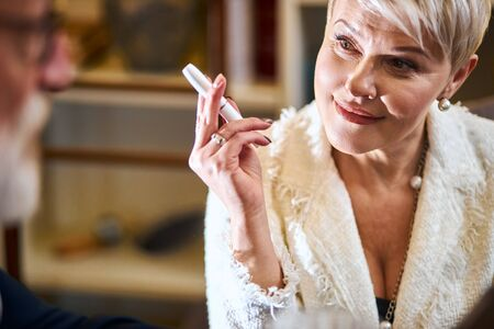 Elderly grey-haired woman in white blazer use electronic cigarette in restaurant, close-up. Old generation and modern technologies, devices. Looks at man