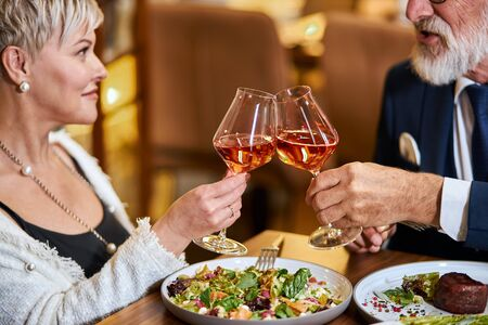 Beautiful elderly couple have a meal in personable restaurant, in love. Grey-haired male and female drink and clink glasses with champagne.