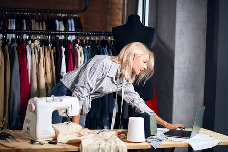 young seamstress surfing, browsing the net while working at studio. close up side view photo Stock Photo