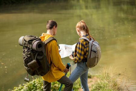 Couple backpackers standing near the lake, styding the map. back view photo. close up portrait, travle, tourism