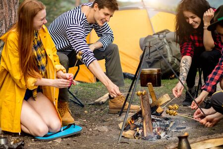 young positive travellers preparing a snack outdoors. close up side view photo. Фото со стока