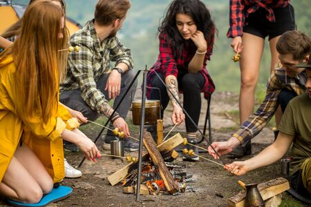 a company of young people cooking mushrooms on fire outdoors. friendship, food. close up cropped photo