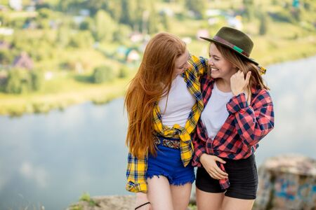 crazy funny sisters in stylish shirts and shorts having fun on the top of rock, free time, spare time, lifestyle, copy space