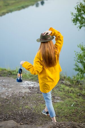slim attractive girl in stylish raincoat lightning the top of mountain in the evening, backview full length photo