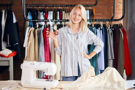 cheerful blonde woman holding scissors in hands, going to cut textile. close up photo Stock Photo