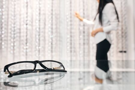 Glasses, Eyeglasses Optical Store, Fashion eyewear lying on the table market, woman standing next to shelf with many glasses, close up cropped photo. blurred background, studio shot