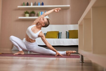 Beautiful female enjoy practicing yoga at home. Support healthy lifestyle, everyday working out Banco de Imagens