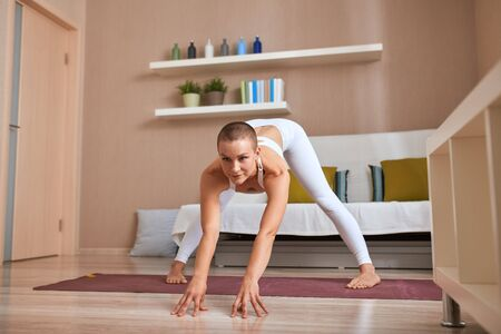 Yoga position demonstrated by beautiful caucasian girl, dressed in white topic and leggins, practice in light room, legs apart.