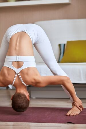 Woman exercise yoga as a hobby at home. Female in white sporty suit support healthy lifestyle