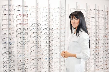 smiling confident successful optician in white medical coat preasenting new collection of glasses. close up photo. copy space