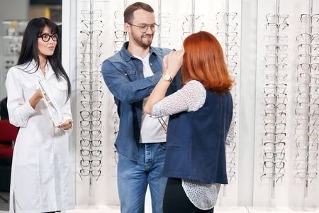 ginger woman is trying on a new pair of glasses, her boyfriend is helping her while asian beautiful optician holding a mirror. close up photo Banco de Imagens
