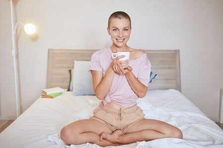 Happy short-haired caucasian girl woke up and drink cup of tea. Female in t-shirt and shorts with crossed legs on bed. Background light room. Banco de Imagens