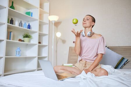 Attractive caucasian girl with short hair sit on white bed with laptop and headphones. Apple in hands. Happy