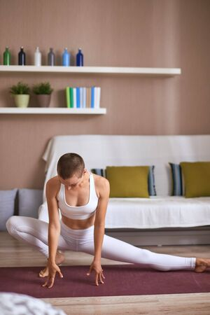 Slim young girl doing yoga exercises at home. Dressed in white leggins and topic, practice stretching. Keep muscles in tonus