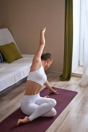 Woman with legs crossed in white clothing stretching at home on mat, doing yoga or pilates. Slim and attractive body 스톡 콘텐츠
