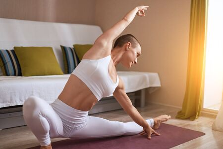 Plastic caucasian girl practice split yoga, do exercise at home in white sportswear. Background sofa in livingroom