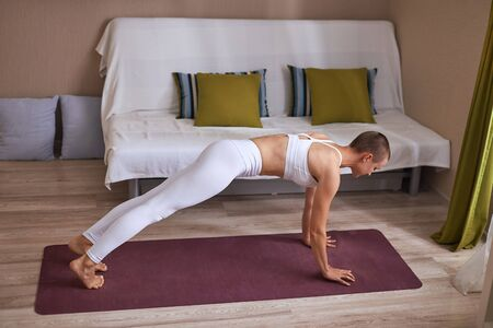 Sporty woman in white sportswear rise body up, do exercises at home