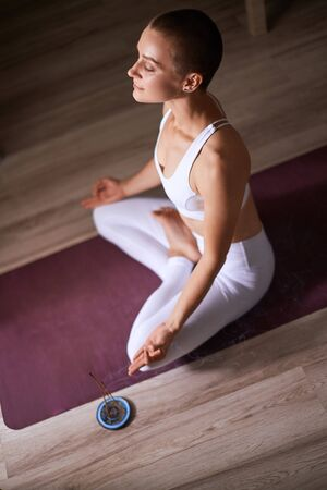 Short-haired young woman sit in lotus pose on mat with candles for yoga. Dressed in white leggins and topic. Meditating. Yoga, healthcare concept