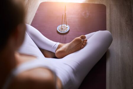 Woman in white leggins sits with crossed legs on mat, candles in front of her. Yoga, healthy lifestyle concept Banco de Imagens