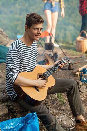 young cheerful handsome talented tourist playing the guitar, close up photo. art, hobby, interest, active lifestyle