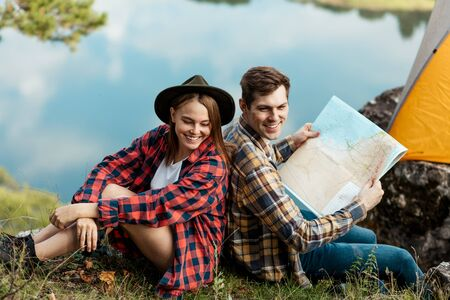 handsome positive man and beautiful woman in stylish checked shirts sitting back to back, having fun outdoors. close up side view photo, free time spare time