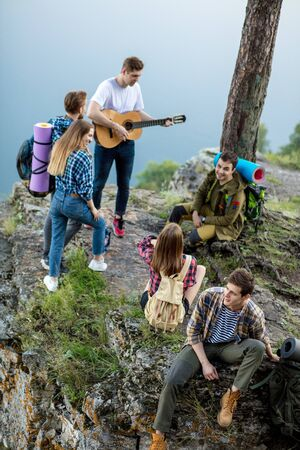 ambitious active travellers playing the guitar, singing songs in the fresh air, fun concept
