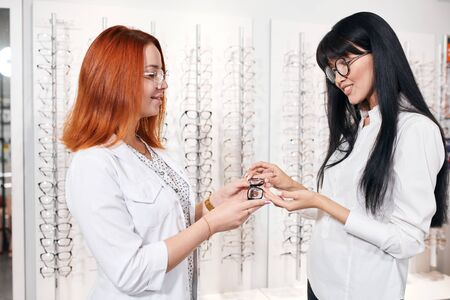 ginger optometrist helping a pretty Asian client to try on and purchase frames for a pair of eyeglasses, close up side view photo.lifestyle,job, profession