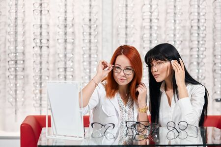 good looking two girls trying on eyewears, close up photo. lifestyle