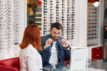 handsome customer choosing appropriate eyeglasses at store, lifestyle, business, sale, discount. close up photo Banco de Imagens