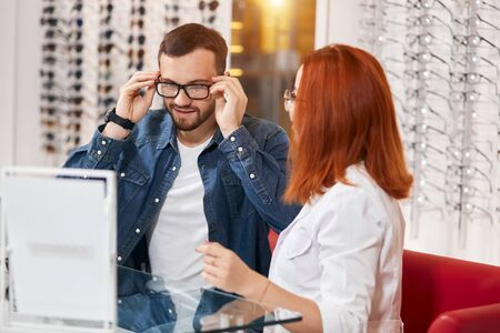 handsome male client enjoying choosing glasses at clinic, . bargain, medicine concept, close up photo