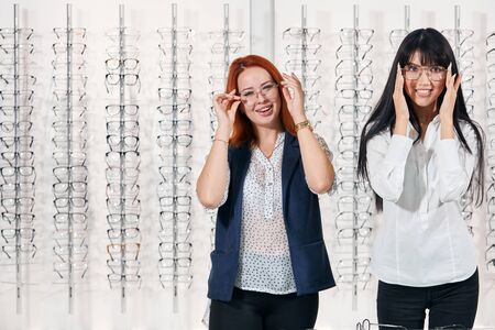 positive cheerful girls having fun at optics. close up photo. copy space. girls touching glasses and posing to the camera