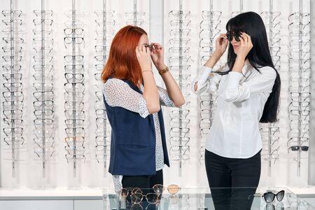 young women comparing glasses. putting on eyewears, selecting sunglasses. close up photo Фото со стока