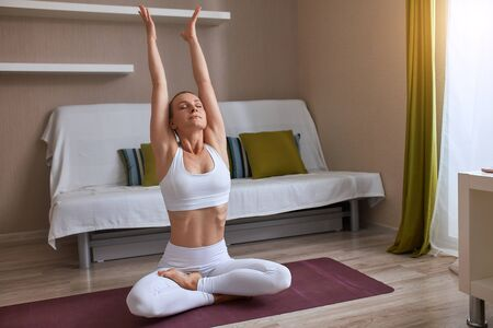 Attractive short-haired woman practice yoga and raised hands mudra, keep fit everyday. Best way to to begin day. Healthy lifestyle concept