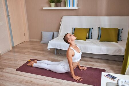 portrait of beautiful woman doing yoga at home. One leg is raised. People, healthy lifestyle concept
