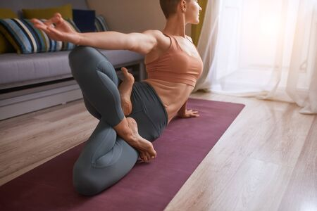 Short-haired woman in grey leggins practice yoga in room. Female sit on one crossed leg, another leg above.