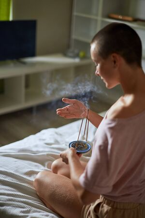 Beautiful female sit on bed and relax smoking insence yoga sticks. Background bedroom at home Imagens