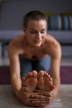 Close up female feet while stretching on mat. Stretching in Seated forward bend exercise, paschimottanasana pose. Cheerful woman clothed in sportswear