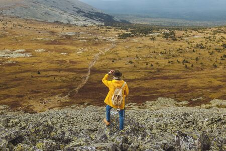 active h iker with backpack relaxing on top of a mountain and enjoying sunset. back view full length photo Stock fotó