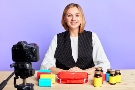 Charming young healthcare company representative posing in front of camera during online conference, holding presentation of new dietary food supplements, vitamins and pills, smiling friendly.