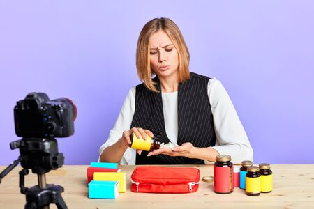Popular healthcare female consultant prepares new video content about medical kit for her blog, empties out bottle with drugs, handful of pills, thoughtful and focused face expression, studio shot. Zdjęcie Seryjne