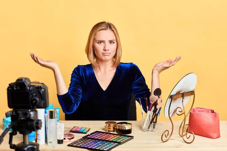 Surprised blonde female makeup artist looks with puzzlement, shruggs shoulders and spreads hands, feels clueless and uncertain, dissatisfied with something unpleasant. Emotions and massmedia concept. Stockfoto