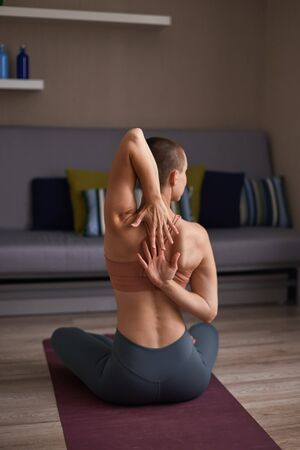 Athletic woman in topic and leggins stretch hands sitting at home on purple mat. Flexible and sporty female