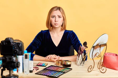 Close up portrait of bothered female cosmetic company representer sitting in front of the camera before online presentation of makeup products, has hopeful miserable expression, purses lips nervously. Stock fotó