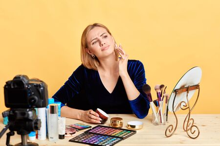 Dissatisfied blonde female cosmetics expert applies new face cream on her cheek, doesnt like the texture and fragrance of the products, frowns in dislike, recording content for her beaty blog. Stockfoto