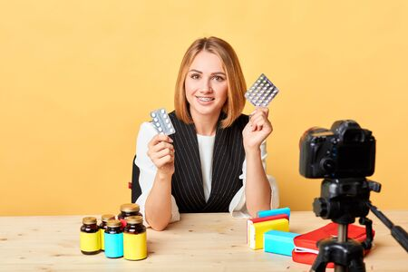 Popular lifestyle blogger girl recording video about her first-aid kit contents, describing pills, supplements and drugs she has in it, holding two packs in hands, gazing in camera with gentle smile.