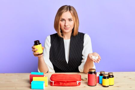 Cute friendly female doctor presents diverse health and beauty supplements, handful of pills, looks at camera with gentle smile, isolated studio shot. People, healthcare and drugs concept.