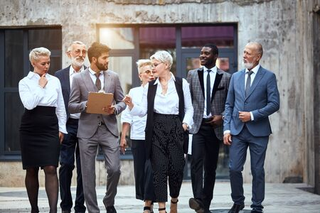 Group of businessmen dressed in stylish office clothes discuss project and move in street. Taken full length