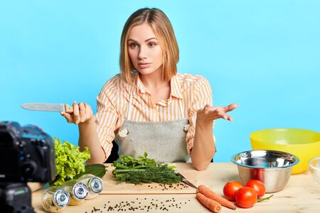 Isolated view of young cute female chef telling cooking hacks to followers while recording online culinary master class for her food blog, spreading hands, making fresh salad with various vegetables.