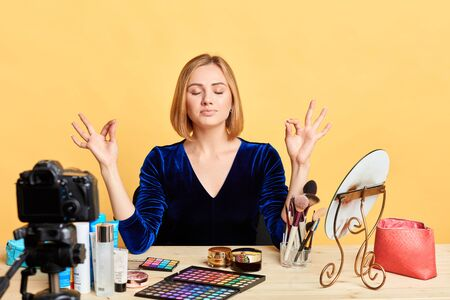 Optimistic young female makeup artist meditates before shooting her video master class, tries to calm down and to keep mind clear, makes yoga breath exercise. Blogging, people and emotions concept. Stockfoto