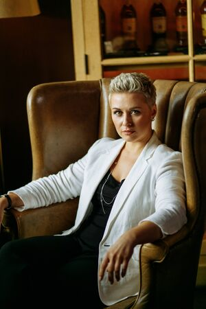 Portrait of beautiful young strict businesswoman in unbuttoned white jacket, sitting relaxed on noble beige armchair putting elbows on armrest, looking towards camera with smiling talking eyes